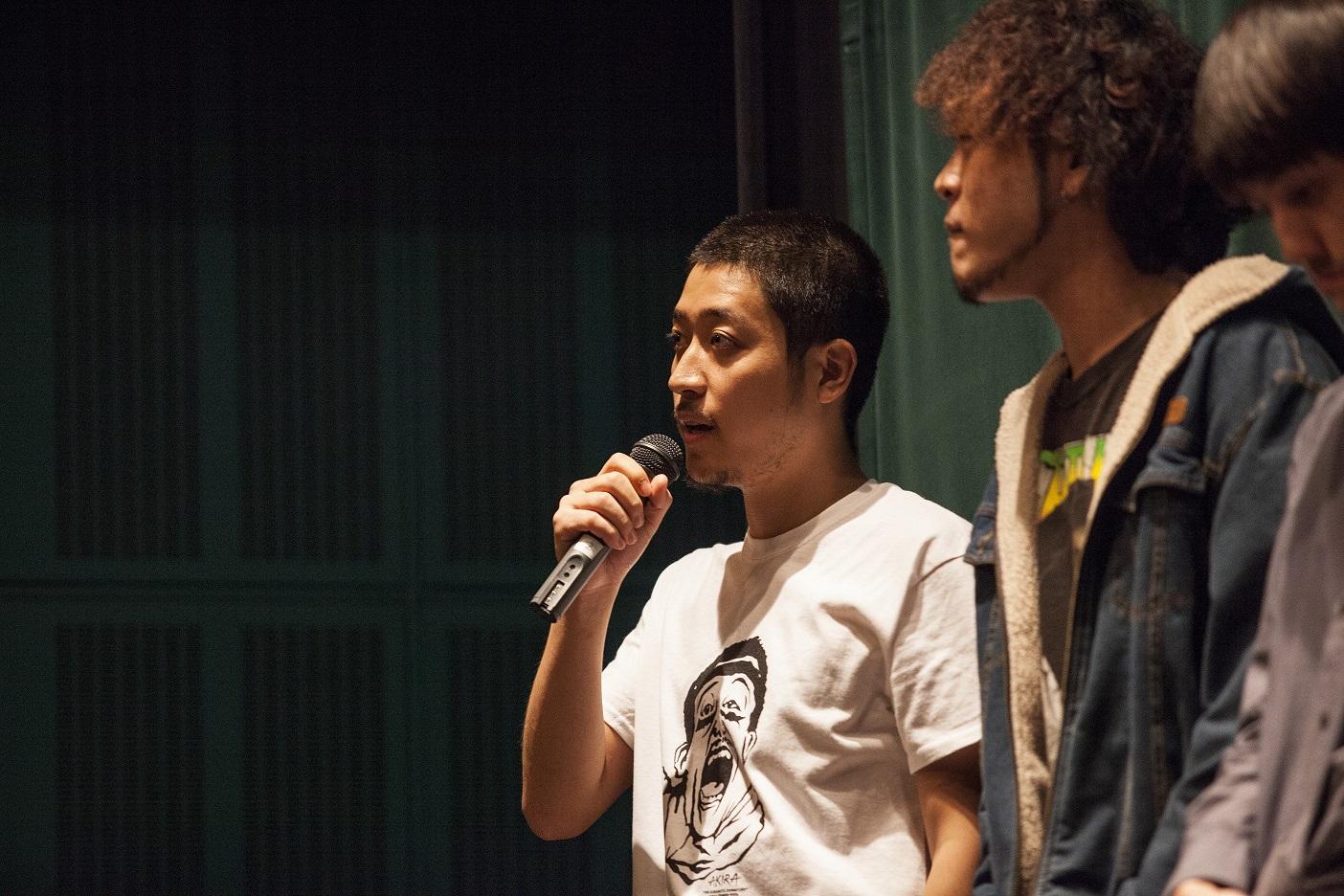 故郷の詩_初日舞台挨拶 (4)  初日舞台挨拶で話す嶺豪一監督。トップ写真は先行上映会でゲストの